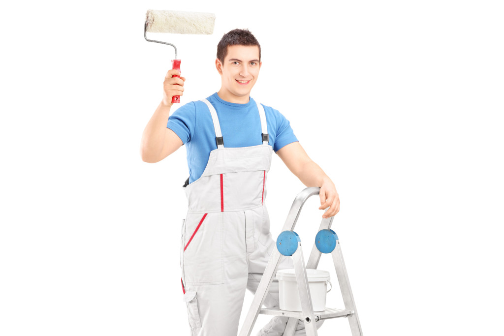 Male painter holding a roller and standing on a ladder isolated